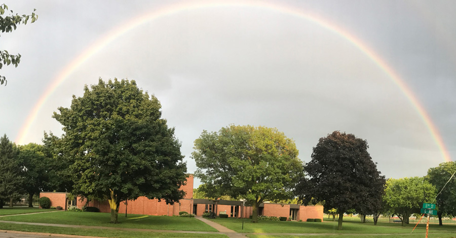 Exterior image of Memorial Lutheran Church with a full rainbow above